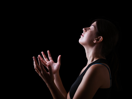 Low key of a faithful woman praying and feeling the presence or being touched by god. Arms outstretched in worship, head up and eyes closed in religious fervor. Black background. Imagens