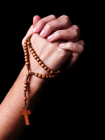 Female hands praying holding a beads rosary with a cross or Crucifix on black background. Woman with Christian Catholic religious faith. Profile or side view