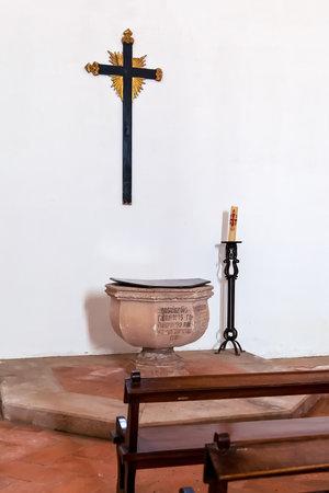 Santarem, Portogallo - 11 settembre 2017: Fonte battesimale gotica, croce o crocifisso e banchi nella chiesa Igreja de Santa Clara. Architettura gotica mendicante del XIII secolo