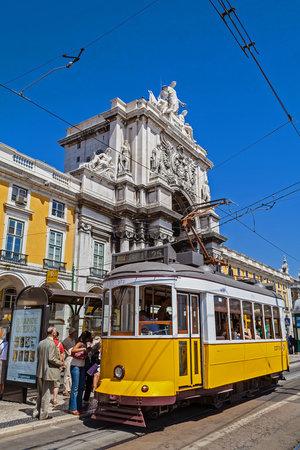 Lisbon, Portugal - September 4, 2018: Carris vintage yellow tram and Rua Augusta Street Triumphal Arch in Praca do Comercio aka Commerce Square or Terreiro do Paco