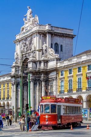 Lisbon, Portugal - April 14, 2018: Carris vintage yellow tram and Rua Augusta Street Triumphal Arch in Praca do Comercio aka Commerce Square or Terreiro do Paco