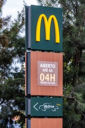 Coina, Portugal - October 23, 2019: Signboard of McDonald's with Golden Arches at the entrance of a McDonalds restaurant informing of the McDrive drive thru service and serving hours