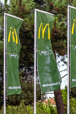 Coina, Portugal - October 23, 2019: McDonald's flags with Golden Arches and the McDrive drive thru service symbol at the entrance of a McDonalds restaurant Editoriali