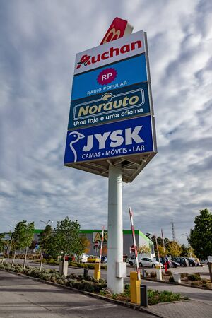 Coina, Portugal - October 23, 2019: Tall advertising pillar or column marketing shops in the Barreiro Planet Retail Park. Editoriali