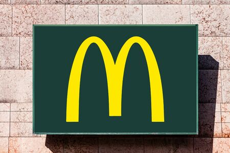Almada, Portugal - October 24, 2019: Signboard advertising McDonald's restaurant with the Golden Arches logo in yellow and green, in a shopping center or shopping mall exterior wall