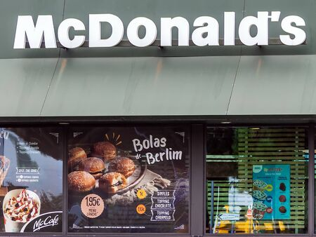 Coina, Portugal - October 23, 2019: Storefront of the McDonalds restaurant and McCafe advertising a sweet pastry called Bolas de Berlim, a regional Portuguese specialty