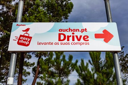 Coina, Portugal - October 23, 2019: Auchan Drive logo or symbol pointing to the pickup area of online purchases. French hypermarket, supermarket or superstore chain. Barreiro Planet Retail Park.