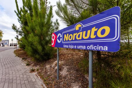 Coina, Portugal - October 23, 2019: Signpost pointing to Norauto car or auto parts shop and service station. Auto repair shop in Barreiro Planet Retail Park. The text says: One store and one workshop Editoriali