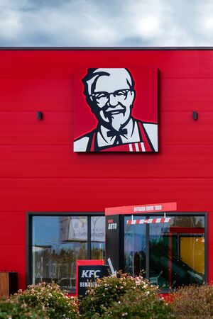 Coina, Portugal - October 23, 2019: Colonel Sanders logo or symbol on the facade of a KFC fast food restaurant. Kentuky Fried Chicken junk food in Barreiro Planet Retail Park