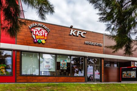 Coina, Portugal - October 23, 2019: Entrance of KFC fast food restaurant with an ad for the Tasty World children area (�rea Infantil in Portuguese). Kentuky Fried Chicken junk food in Barreiro Planet Retail Park Editoriali