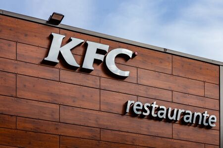 Coina, Portugal - October 23, 2019: KFC lettering on the facade of a Kentuky Fried Chicken fast food restaurant. Junk food restaurant in Barreiro Planet Retail Park