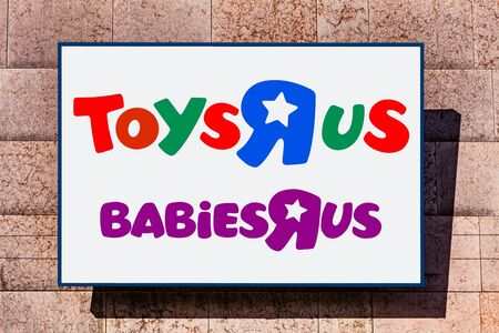 Almada, Portugal - October 24, 2019: Signboard advertising the ToysRus and BabiesRus, babies, and children toy store in a shopping center or shopping mall exterior wall.