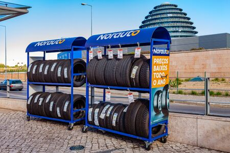 Almada, Portugal - October 24, 2019: Tires on rack at Norauto car or auto parts shop and service station or auto repair shop in Almada Forum shopping mall or center. Norauto is a French company