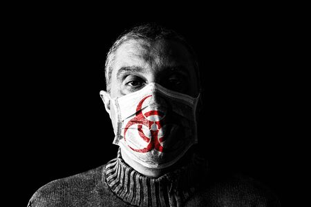 Man with surgical mask with biohazard or biological hazard symbol. Pandemic or epidemic and scary, fear or danger concept. Black Background