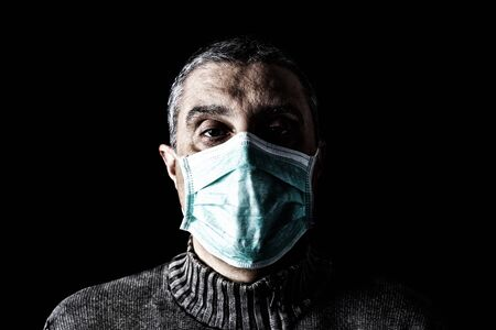 Man with surgical mask. Pandemic or epidemic and scary, fear or danger concept. Protection for biohazard like COVID-19 aka Coronavirus. Black Background