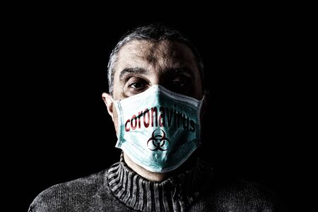 Man with surgical mask. Biohazard and Coronavirus, aka COVID-19 symbol. Pandemic or epidemic and scary, fear or danger concept. Black Background