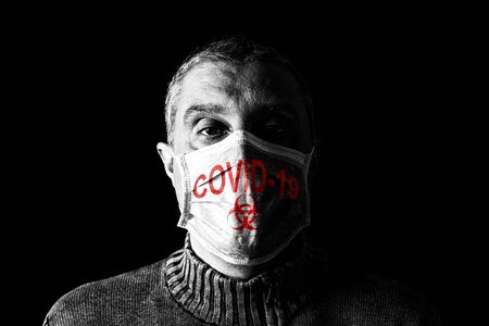 Man with surgical mask. Biohazard and COVID-19, aka Coronavirus symbol. Pandemic or epidemic and scary, fear or danger concept. Black Background