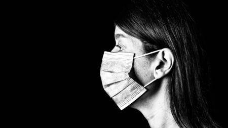 Woman with surgical mask. Pandemic or epidemic and scary, fear or danger concept. Protection for biohazard like COVID-19 aka Coronavirus. Close-up profile  portrait. Black Background. Black and White Archivio Fotografico