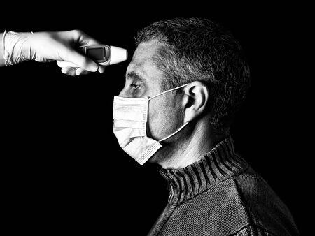 homme ayant la fièvre mesurée ou prise avec un thermomètre numérique par une infirmière. Concept de pandémie ou d'épidémie, effrayant, peur ou danger. Protection contre les risques biologiques comme COVID-19 aka Coronavirus. Noir et blanc