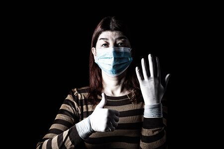 Woman with surgical mask, protective gloves and thumbs up. Pandemic or epidemic and scary, fear or danger concept. Protection for biohazard like COVID-19, Coronavirus, Ebola. Black Background Archivio Fotografico