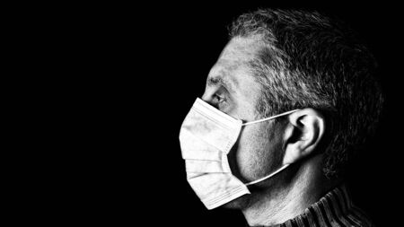 Man with surgical mask. Pandemic or epidemic and scary, fear or danger concept. Protection for biohazard like COVID-19 aka Coronavirus. Close-up profile  portrait. Black Background. Black and White.
