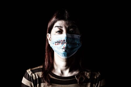Woman with surgical mask. Biohazard and Coronavirus, aka COVID-19 symbol. Pandemic or epidemic and scary, fear or danger concept. Black Background