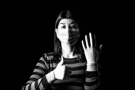 woman with surgical mask, protective gloves and thumbs up. Pandemic or epidemic, scary, fear or danger concept. Protection for biohazard like COVID-19, Coronavirus, Ebola. Black Background Black White