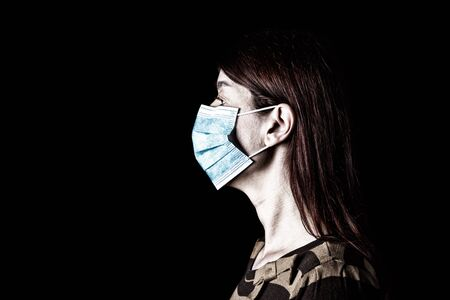 Woman with surgical mask. Pandemic or epidemic and scary, fear or danger concept. Protection for biohazard like COVID-19 aka Coronavirus. Profile portrait. Black Background
