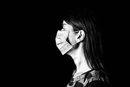 Woman with surgical mask. Pandemic or epidemic and scary, fear or danger concept. Protection for biohazard like COVID-19 aka Coronavirus. Profile portrait. Black Background. Black and White. Archivio Fotografico