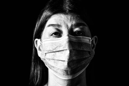 Woman with surgical mask. Pandemic or epidemic and scary, fear or danger concept. Protection for biohazard like COVID-19 aka Coronavirus. Close-up  portrait. Black Background. Black and White.