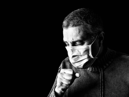 man with surgical mask sneezing or coughing. Pandemic or epidemic and scary, fear or danger concept. Protection for biohazard like COVID-19 aka Coronavirus. Black Background. Black and White