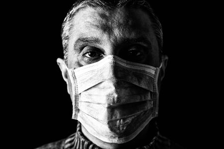 Man with surgical mask. Pandemic or epidemic and scary, fear or danger concept. Protection for biohazard like COVID-19 aka Coronavirus. Close-up  portrait. Black Background. Black and White. Archivio Fotografico