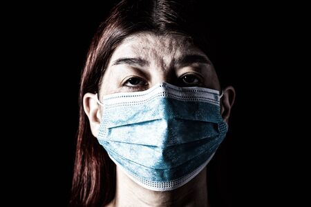 Woman with surgical mask. Pandemic or epidemic and scary, fear or danger concept. Protection for biohazard like COVID-19 aka Coronavirus. Close-up  portrait. Black Background. Archivio Fotografico