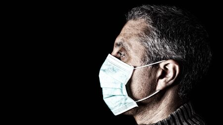 Man with surgical mask. Pandemic or epidemic and scary, fear or danger concept. Protection for biohazard like COVID-19 aka Coronavirus. Close-up profile  portrait. Black Background