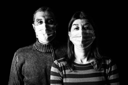 Man and woman with surgical masks. Couple protected with face mask. Pandemic or epidemic, scary, fear,danger concept. Protection for biohazard like COVID-19, Coronavirus, Ebola. Black White Background