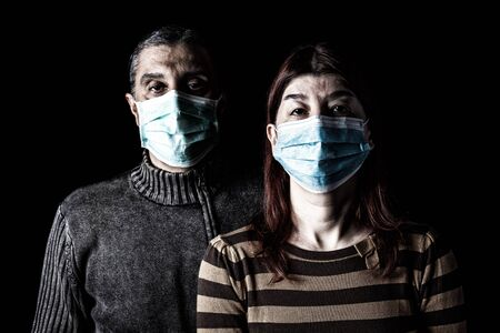 Man and woman with surgical masks. Couple protected with face mask. Pandemic or epidemic, scary, fear or danger concept. Protection for biohazard like COVID-19, Coronavirus, Ebola. Black Background
