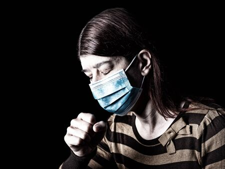 Woman with surgical mask sneezing or coughing. Pandemic or epidemic and scary, fear or danger concept. Protection for biohazard like COVID-19 aka Coronavirus. Black Background Archivio Fotografico