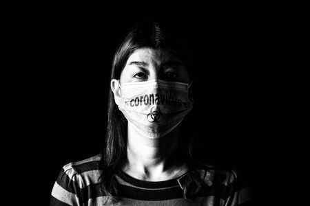 Woman with surgical mask. Biohazard and Coronavirus, aka COVID-19 symbol. Pandemic or epidemic and scary, fear or danger concept. Black and White. Black Background