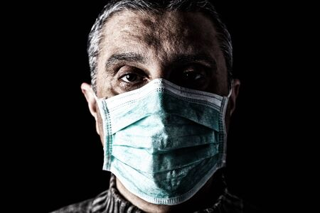 Man with surgical mask. Pandemic or epidemic and scary, fear or danger concept. Protection for biohazard like COVID-19 aka Coronavirus. Close-up  portrait. Black Background. Archivio Fotografico