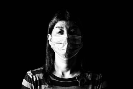 Woman with surgical mask. Pandemic or epidemic and scary, fear or danger concept. Protection for biohazard like COVID-19 aka Coronavirus. Black and White. Black Background Archivio Fotografico