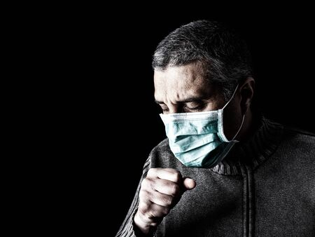 man with surgical mask sneezing or coughing. Pandemic or epidemic and scary, fear or danger concept. Protection for biohazard like COVID-19 aka Coronavirus. Black Background