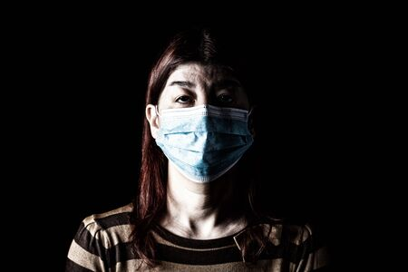 Woman with surgical mask. Pandemic or epidemic and scary, fear or danger concept. Protection for biohazard like COVID-19 aka Coronavirus. Black Background