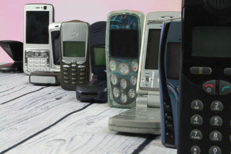 Old mobile phones arranged on wooden