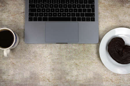 Top view of a computer accompanied by a tablet, a mobile phone and coffee with scones on an abstract background