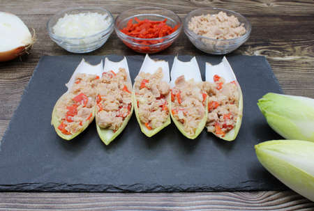 Endives dish filled with tuna, red pepper and onion