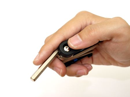 hex key: Pocket cyclist hex key in male hand on white background