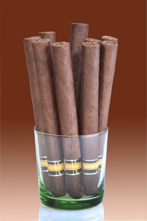 Nine long cigars in a glass photo