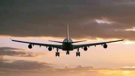 airport runway: Airplane before landing in sunset Stock Photo