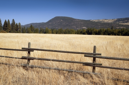 Field in Okanagan -fence in the field and mountains photo