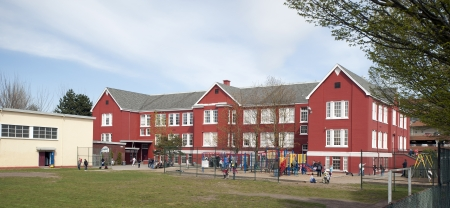 old building facade: Historic school with a playground